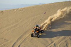 Man Riding Atv In Desert. Young man riding ATV over sand dune in desert stock photography