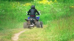 Unknown man wearing protective suit riding ATV or quad on a dusty outskirts road. Man riding ATV on a dusty field road. Slow motion shot stock video