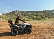 A man riding ATV in sand in a  helmet. Royalty Free Stock Images