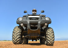 A man riding ATV in sand in a  helmet. Stock Photography