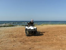 A man riding ATV in sand in a  helmet. Royalty Free Stock Image