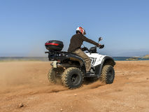 A man riding ATV in sand in a  helmet. Royalty Free Stock Photos