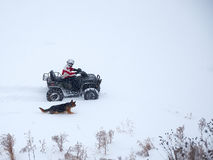 Man riding ATV in the winter with dog. Man riding ATV in the winter with a dog Royalty Free Stock Image
