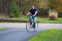 Man Riding Bicycle. Handsome young man riding a bicycle for pleasure and exercise in a rural setting stock photography