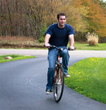 Man Riding Bicycle. Handsome young man riding a bicycle for pleasure and exercise in a rural setting royalty free stock image