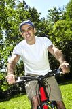 Man riding a bicycle. Happy middle aged man riding a bicycle in summer part Stock Photography
