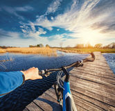 Man riding on a bicycle across the bridge Stock Images
