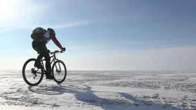 A man riding a bicycle across a frozen lake stock video footage