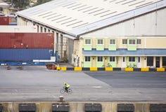 Man Riding Bicycle Across Shipping Dock Stock Image