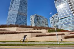 A man is riding a bicycle against the background of high-rise buildings. Sunny day Stock Image
