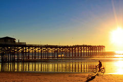 Man riding bicycle along beachfront during a Pacific Ocean sunset in San Diego Stock Image