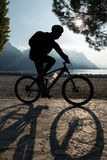 Man Riding Bicycle. Man riding a bicycle along the shore of a lake, silhouetted by the afternoon sun. Rival del Garda, Trentino, Italy royalty free stock images