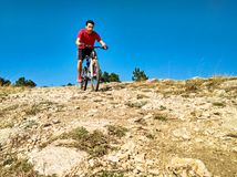Man riding bicycle on rocky mountain. Man riding bicycle at blue sky background. Extreme downhill on rocky mountain Royalty Free Stock Image