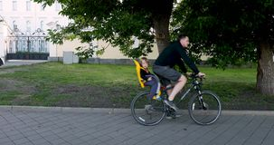 Man riding bicycle with child in safety seat stock video