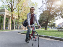 Man riding a bicycle in the city park Stock Images