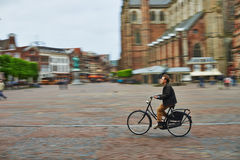 Man riding bicycle in city square Royalty Free Stock Images