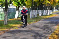 Man riding a bicycle. An elderly man riding a bicycle through the alley in Gome, Belarus Royalty Free Stock Photos