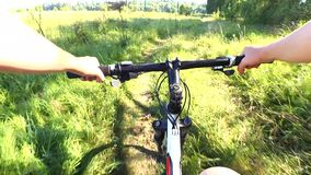 Man riding a bicycle in a field on a green grass. Man riding bicycle in a field on a green grass sunny day summer. Hands and helm. Concept activity, health stock video footage