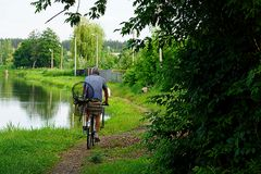 A man riding a bicycle with fishing gear Royalty Free Stock Photography