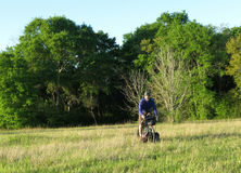 Man riding bicycle in green meadow. Man riding bicycle over grass field with trees in background Stock Image