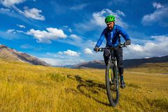 A man is riding a bicycle in the mountains. Autumn in the mountains. Kyrgyzstan stock photo