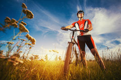 Man is riding bicycle outside in the field Stock Photos