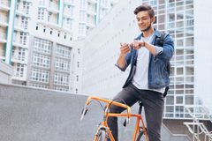 Man riding a bicycle outside. Happy guy stopped to take nice picture of the interesting building or he is just scrolling on his mobile phone. Urban background Royalty Free Stock Image