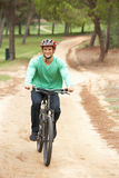 Man riding bicycle in park. Looking forward Royalty Free Stock Photo