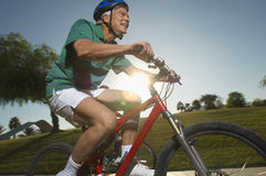 Man Riding Bicycle In Park. Happy man riding bicycle in park at dusk Royalty Free Stock Images