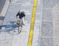 Man riding bicycle on pedestrian pathway in city stock photo