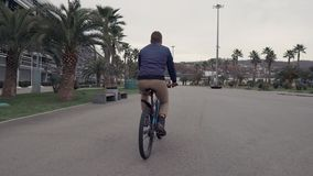 Man is riding on bicycle in summer day over road in tropical city, back view stock video
