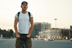 Man riding bicycle in urban city holding hands on handlebar, blurred city in background. Portrait of a young man riding on bicycle in the city road, street with stock image