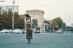 Man riding bicycle in urban city holding hands on handlebar stock image