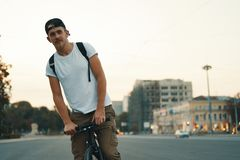 Man riding bicycle in urban city holding hands on handlebar stock photography