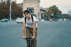 Man riding bicycle in urban city holding hands on handlebar stock images