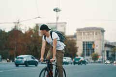 Man riding bicycle in urban city holding hands on handlebar royalty free stock photos