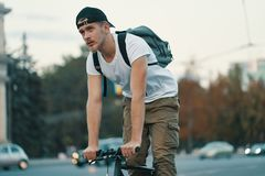 Man riding bicycle in urban city holding hands on handlebar. Portrait of a young man riding on bicycle in the city road, street with city far in the background royalty free stock photos