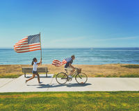 Man Riding a Bicycle Wearing American Flag Beside a Woman Running Holding American Flag Near Seashore during Daytime Royalty Free Stock Photos