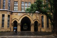 Arch doors at University of Tokyo. Man riding bicyle pass Path way of antique arch doors at University of Tokyo, Japan. Here, called Todai, is the first ranked Royalty Free Stock Photo