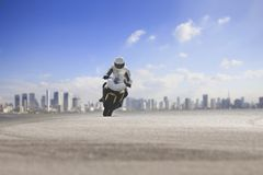 Man riding big motorcycle on asphalt highway against urban skyline background royalty free stock photography