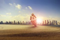 Man riding big motorcycle on sharp curve against city building s Royalty Free Stock Images