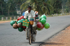 Man riding bike. With plastic water jugs on way to market in Southern India Stock Photography