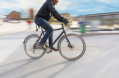 Man riding bike. In blurred motion in city landsacpe Stock Photography