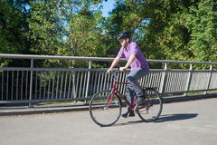 Man Riding on Bike Bridge.psd. A man rides his bicycle along a bike bridge Royalty Free Stock Image