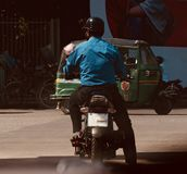Man riding a bike waiting in a traffic signal in Bangladesh. A man riding on a bike in the city streets in Bangladesh unique photo royalty free stock photo