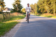 Man riding a bike on the countryside road Royalty Free Stock Photography