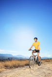 Man riding a bike in a field Royalty Free Stock Photos