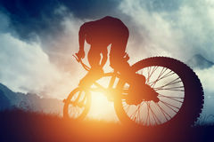 Man riding a bike in high mountains at sunset. Extreme Royalty Free Stock Image