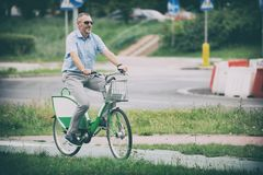 Man riding a city bicycle in formal style. Man riding a bike in his way to work, concept of using city bike as environment friendly way of getting to work Stock Photos