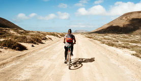 Man riding a bike in La Graciosa, Canary Islands, Spain Royalty Free Stock Photo